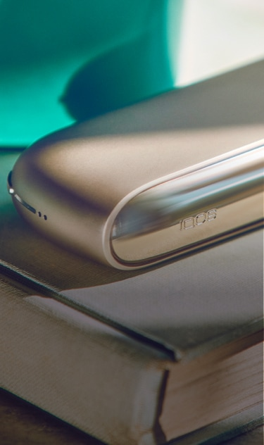 A gold IQOS device and holder on a closed book.